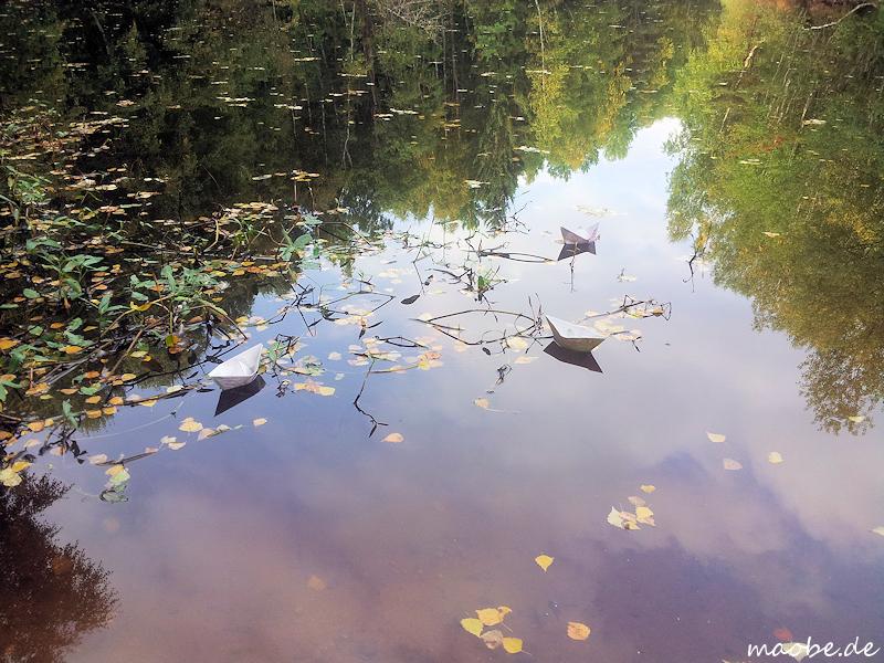 Papierschiffchen auf einem herbstlichen Teich